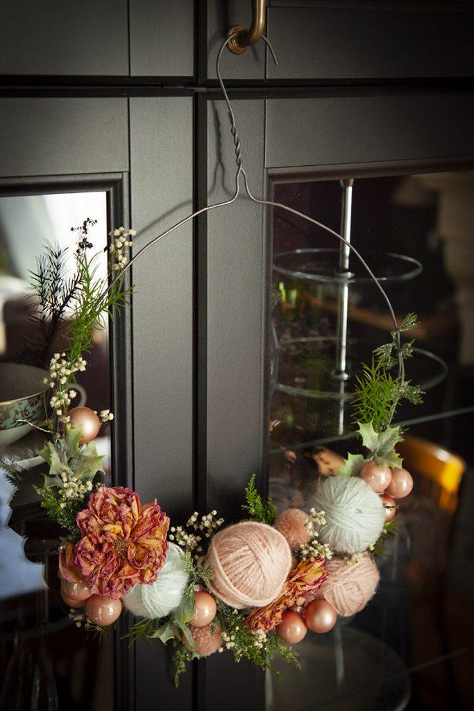 couronne diy réalisée avec un cintre en métal, quelques fleurs séchées et de la laine
